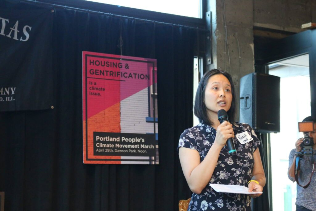 Khanh speaking about community issues at an event in front of a sign that reads